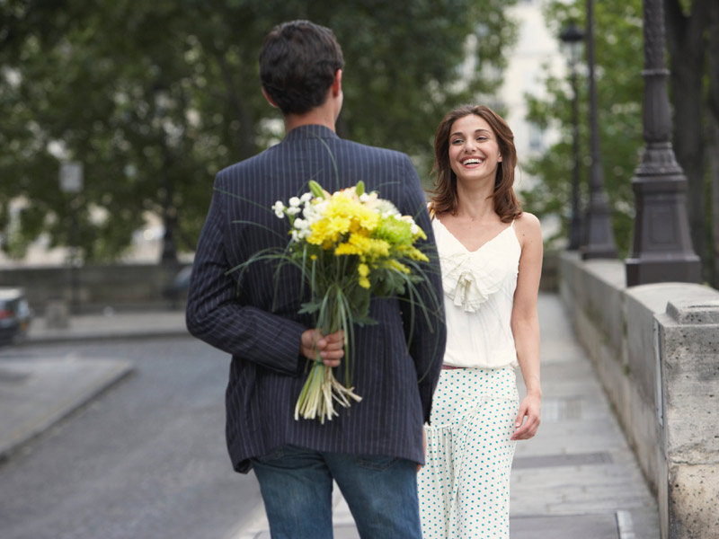 Мужчина дарит девушке цветы